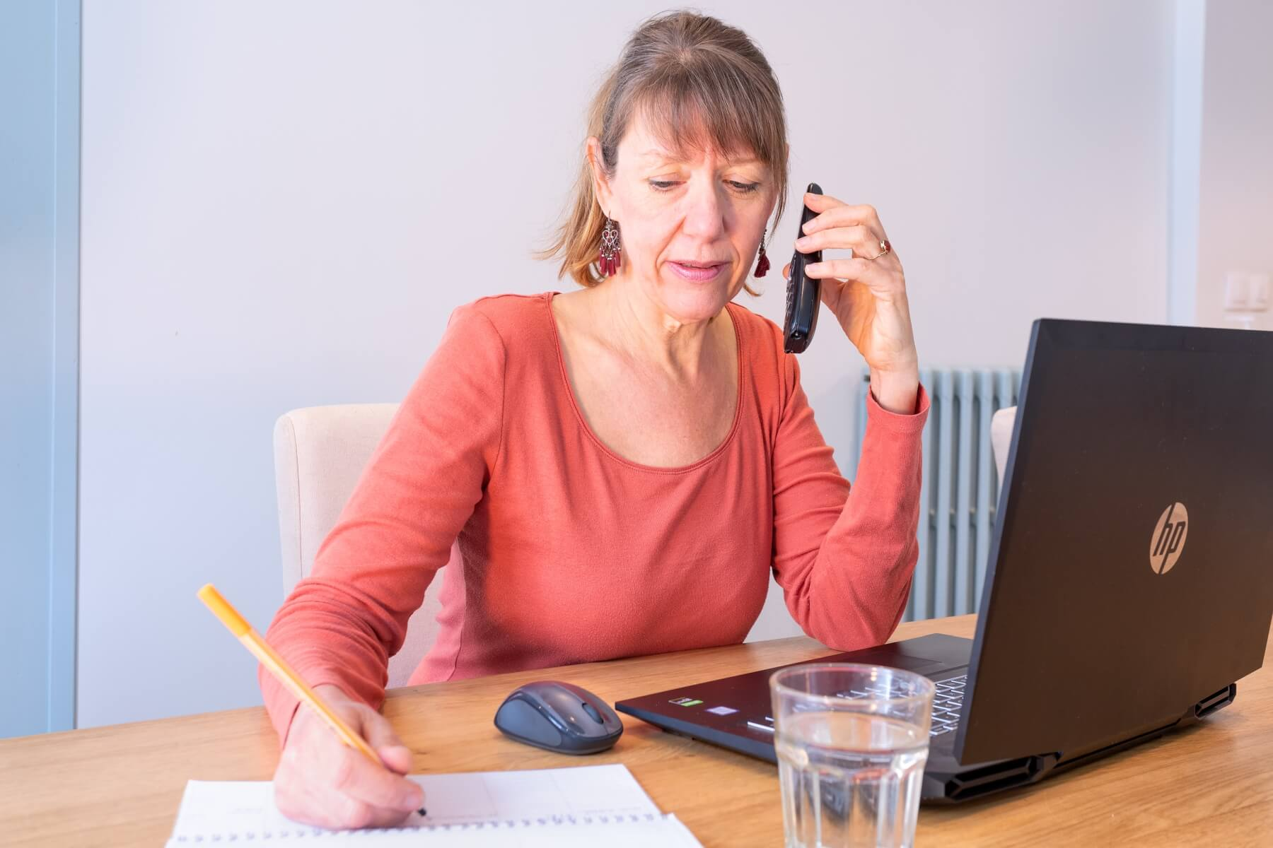 Margriet aan telefoon achter laptop